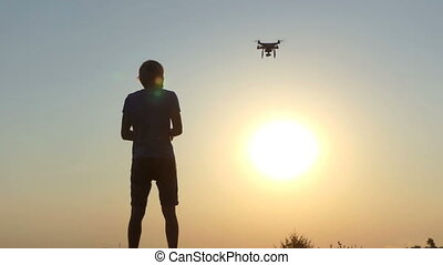 Cameraman operates the flight of a flying drone at sunset in slo-mo