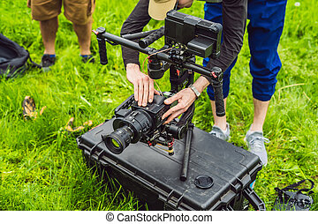 Cameraman setting up heavy duty professional 3-axis gimbal stabilizer for cinema camera