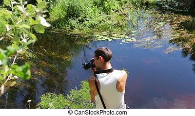 Cameraman shoots a natural river landscape on a video camera...