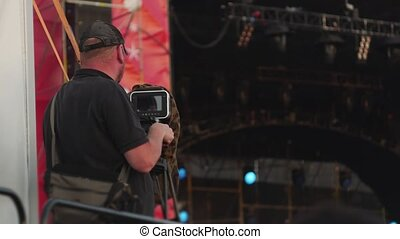 videographer with camera on tripod shoots and broadcasting music festival, behind view