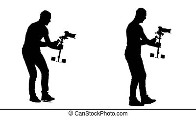 Cameraman steps with the camera and steadicam. White...