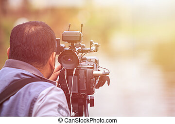 Cameraman using black professional digital video camera. Outdoor setup and working