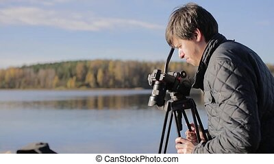 Cameraman with camera on tripod at sunny autumn day outdoors