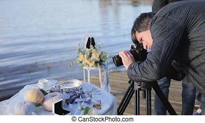 Cameraman with camera on tripod shooting wedding decoration...