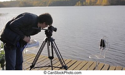 Cameraman with camera on tripod shooting womans shoes -...