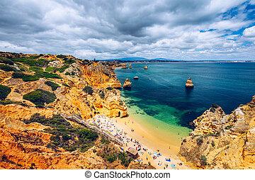 Camilo beach (Praia do Camilo) in Lagos, Algarve, Portugal. Wooden footbridge to the beach Praia do Camilo, Portugal. Picturesque view of Praia do Camilo beach in Lagos, Algarve region, Portugal.