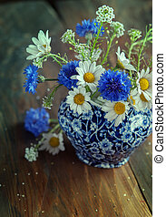 Camomile and cornflowers in a pitcher on table. Flowers from...