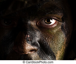 camouflage painted face - young soldier face with jungle...