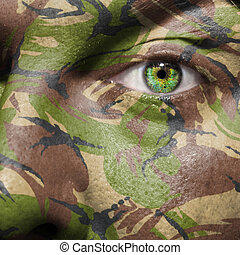 Camouflage painted on a face with green eye to portray ...