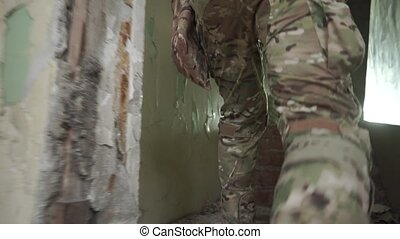 Camouflage wearing soldier sneaking into a hostile ruined building