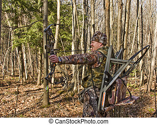 camouflaged bow hunter - bow hunter in camouflage pulling...