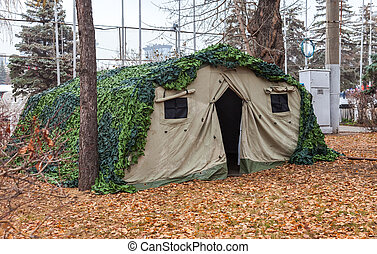 Camouflaged military tent at the autumn park