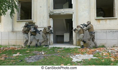 Camouflaged soldiers walking in an abandoned building with weapons during an operational exercise