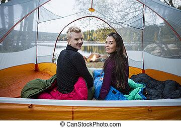 campamento, sentado, lakeside, pareja, durante, tienda