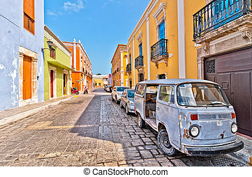 Campeche, Mexico - April 19, 2014: local people, car and motorbikes in downtown street in Campeche, Mexico. The city was founded in 1540 by Spanish conquistadores as San Francisco de Campeche atop the pre-existing Maya city of Canpech