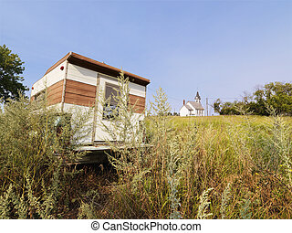 Recreational vehicle in overgrown field with rural church in distance.