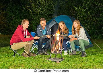 Campfire - A group of friends sitting around a campfire in...