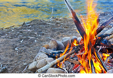 Campfire - A hot campfire burns next to a river.