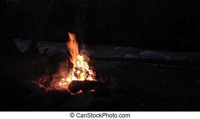 Campfire burns brightly at night along the beautiful beach...