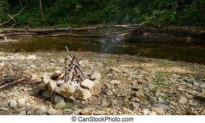 Campfire by the river in a deep wood