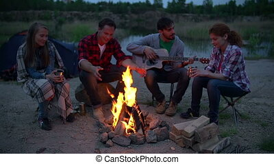 Campfire Stories - Four young friends chilling by fire...