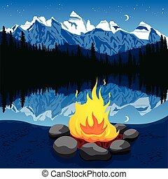 Campfire with stones near mountain lake reflecting night sky