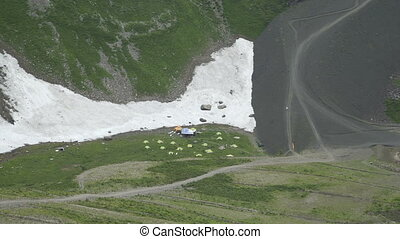 Campground in the snow mountains. Tourists sitting by their...