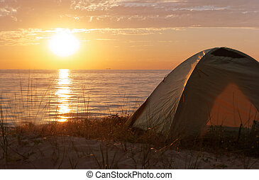 camping at sunset on the sea, tourist tent on the beach