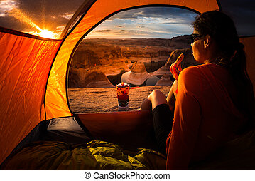 Camping Breakfast Young Woman enjoying a cookie looking at beautiful sunrise Reflection Canyon Lake Powell Utah USA