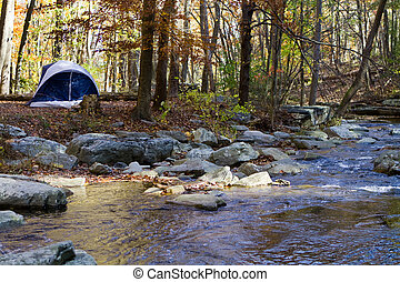 Small camping tent is pitched by a mountain stream in the woods in autumn with fall foliage.