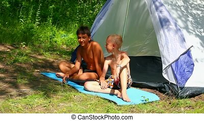 camping children near tent in forest