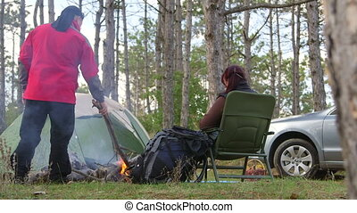 Camping couple resting by campfire