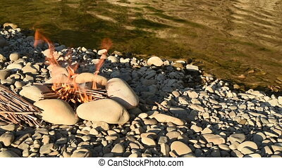Camping fire on the river bank at sunset in the wild.