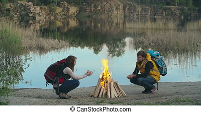 Camping Fire - Side view of two campers crouching at the...