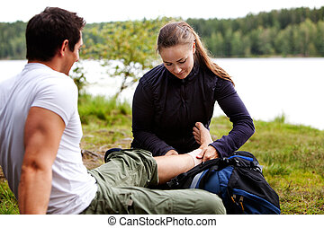 Camping First Aid - A woman applying an ankle bandage on a...