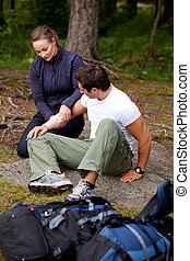 Camping First Aid - A woman applying an arm bandage on a...