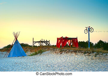 Hippie style camping site with teeppee on the beach