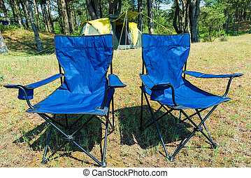 camping in a pine forest by the sea, chairs close-up