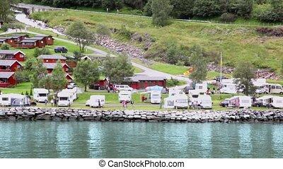 Camping in coastal village near river under mountain