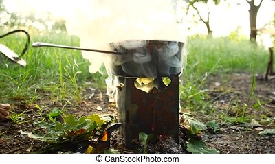 Camping in the forest. A pot of food is boiling on the stove. Smoke comes from the fire.