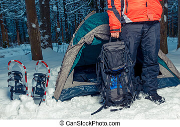 camping in the winter forest, a man with a backpack