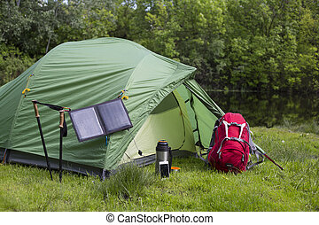 Camping in the woods on the banks of the river. - The solar...
