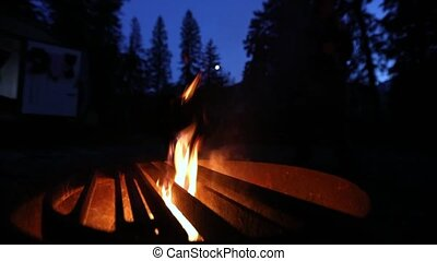 Static camera. Close up on the flickering flames of a fire in a pit. Full moon behind the trees in the blurred background. Night camping scenery.