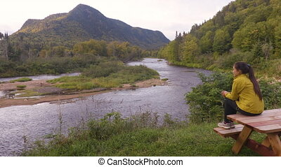 Camping nature woman sitting at picnic table enjoying view of wilderness river in Quebec and autumn foliage forest, Canada travel. Parc de la Jacques-Cartier, Quebec.