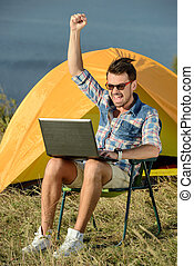 Camping - Portrait of succesful man with laptop sitting in ...