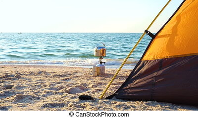 Camping stove and the tent on a sea beach - Camping stove...