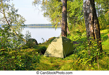 Camping tent on coast of lake.