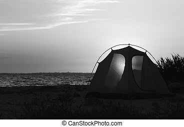 Sea coast and camping tent with shining through entrance on beach at summer evening. Black and white toned landscape.