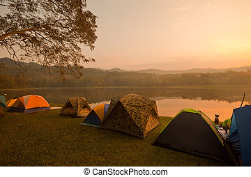 Camping tents by the lake - touristic camp at the evening by...