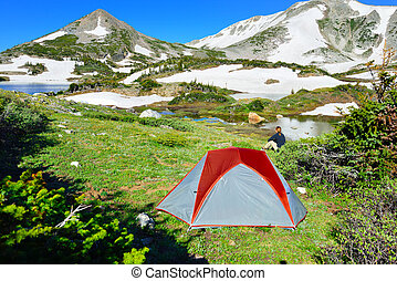 Camping with a tent in Snowy Range Mountains near the lake in Medicine Bow, Wyoming in summer